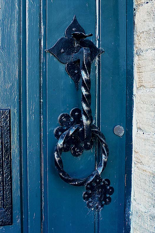 Original wrought iron hardware graces the front door.