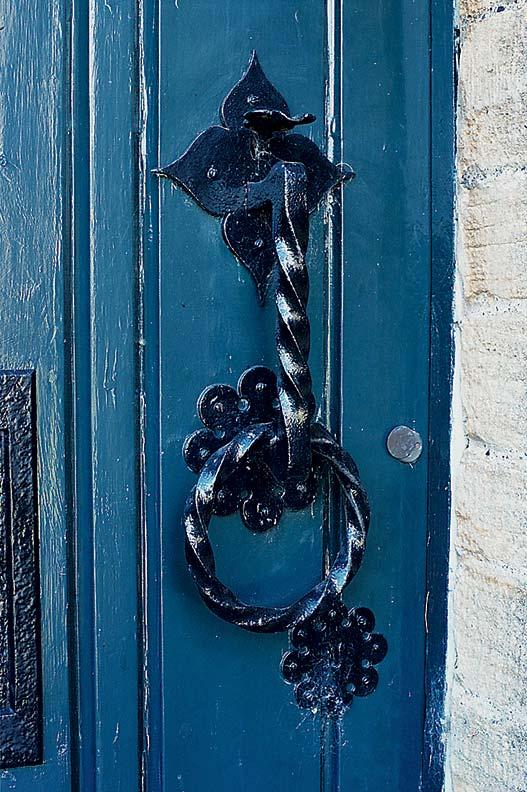 Original wrought iron hardware graces the front door.