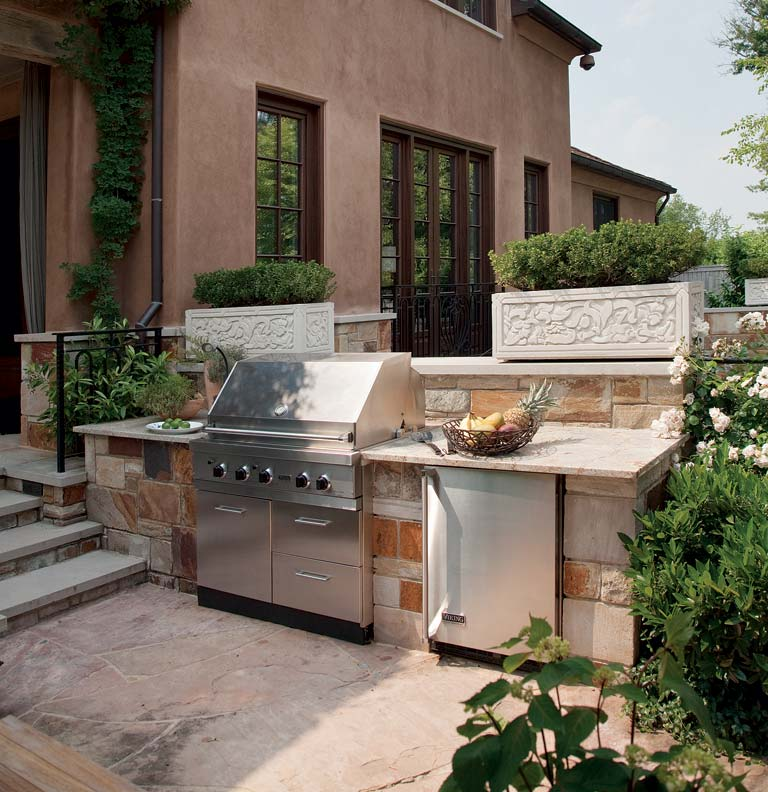 The architects tied the main house and the outdoor kitchen together by using the same colored stone on the house foundation as well as around the grill and refrigerator.