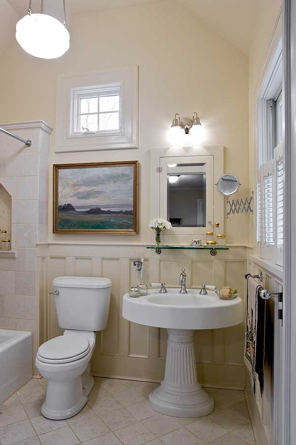 Painted, raised-panel wainscot is carried throughout the house. The oval pedestal sink in the guest bath came from a salvage dealer.
