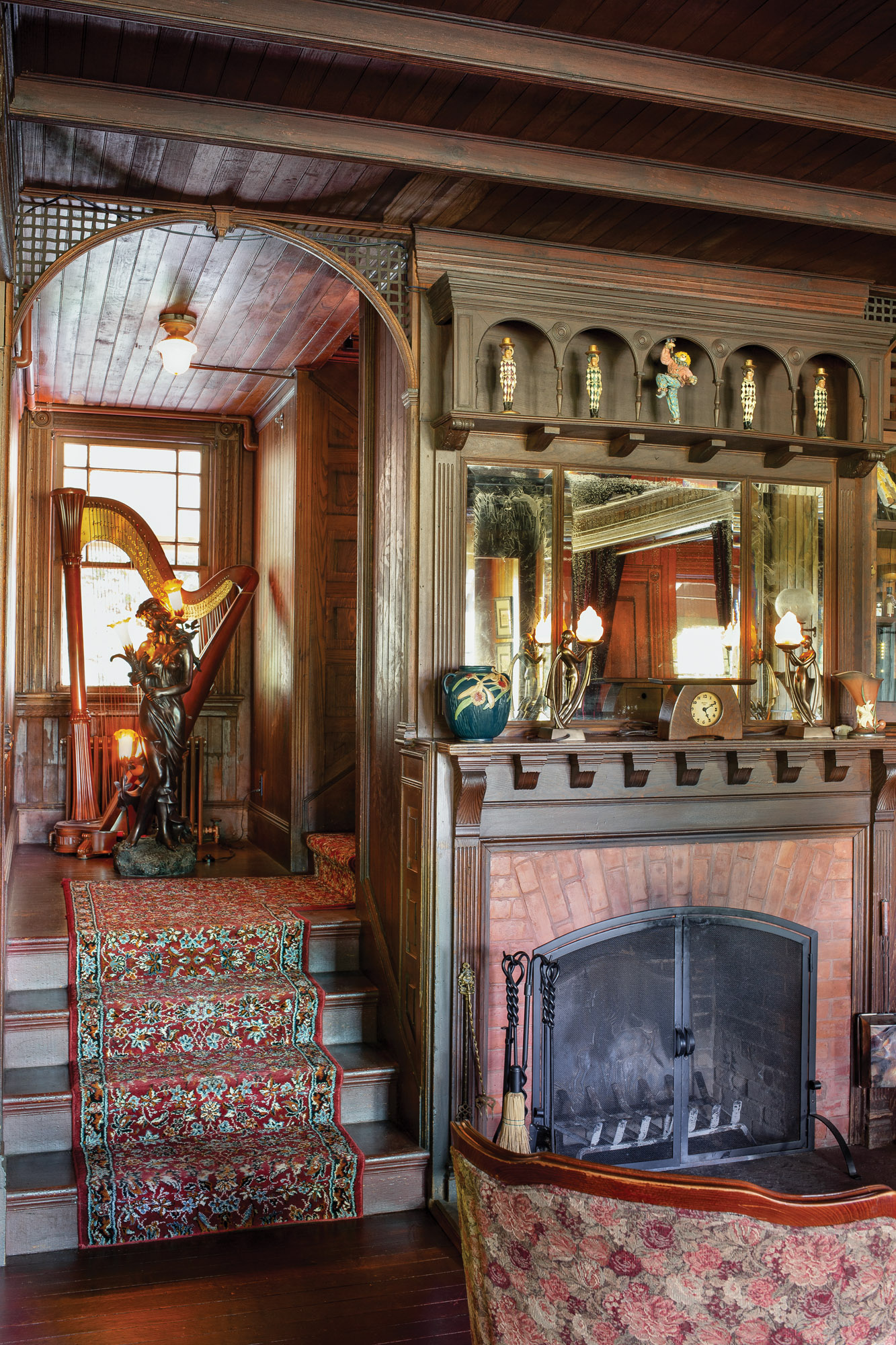 Guests often gather by the fireplace. In the nook leading upstairs sit an antique harp and a spelter maiden, long detached from the newel post in her former home.