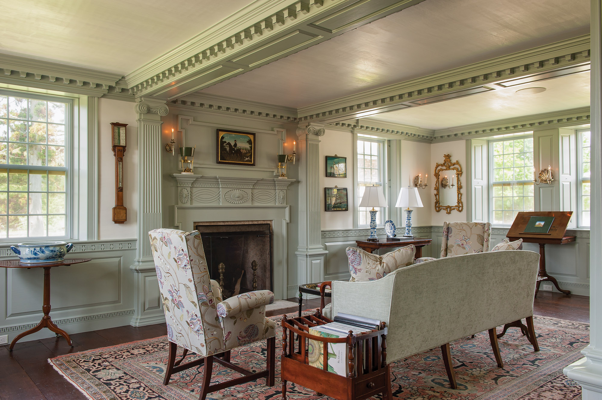The living room's Georgian elements include a fireplace with a bolection moulding surround, pilasters with Corinthian capitals, deep dentil moulding, and a paneled wainscot. Two summer beams accentuate the fireplace wall.