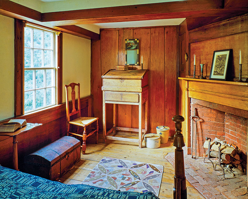 The main bedroom retains its early 19th-century fireplace. Rugs are 20th century.