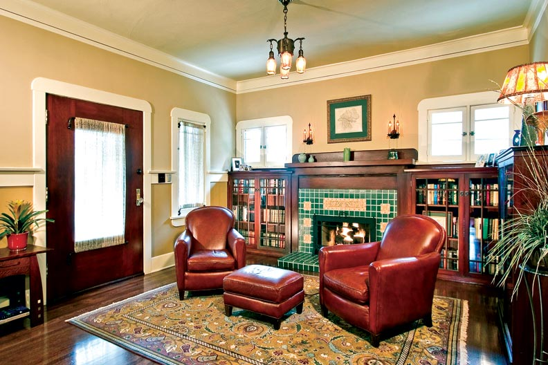 With reproduction Batchelder tiles and glass-fronted bookshelves, the re-created fireplace surround is the focal point of the open den and living room.