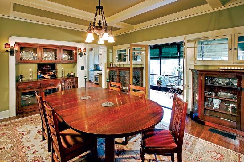 """With refurbished built-in storage, a custom-blended paint color on the walls, and restored vintage lighting, the dining room—which opens to a small screened porch—is one of Anita's favorite rooms in the house. """"It's a wonderful space for entertaining,"""" she says."""