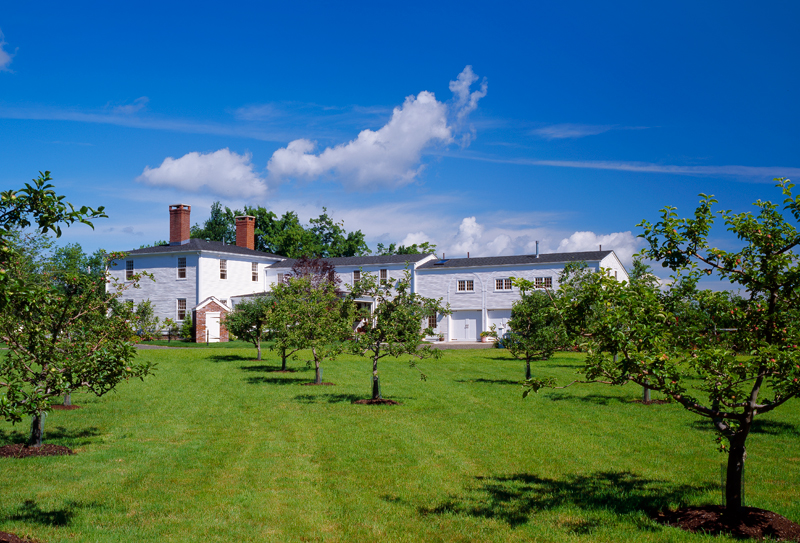 Past the new apple orchard, a view of the house and its additions.