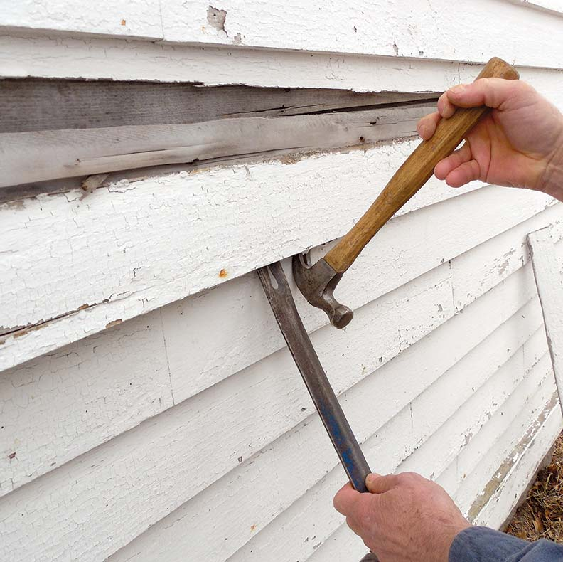 Remove the damaged clapboard with a hammer and pry bar