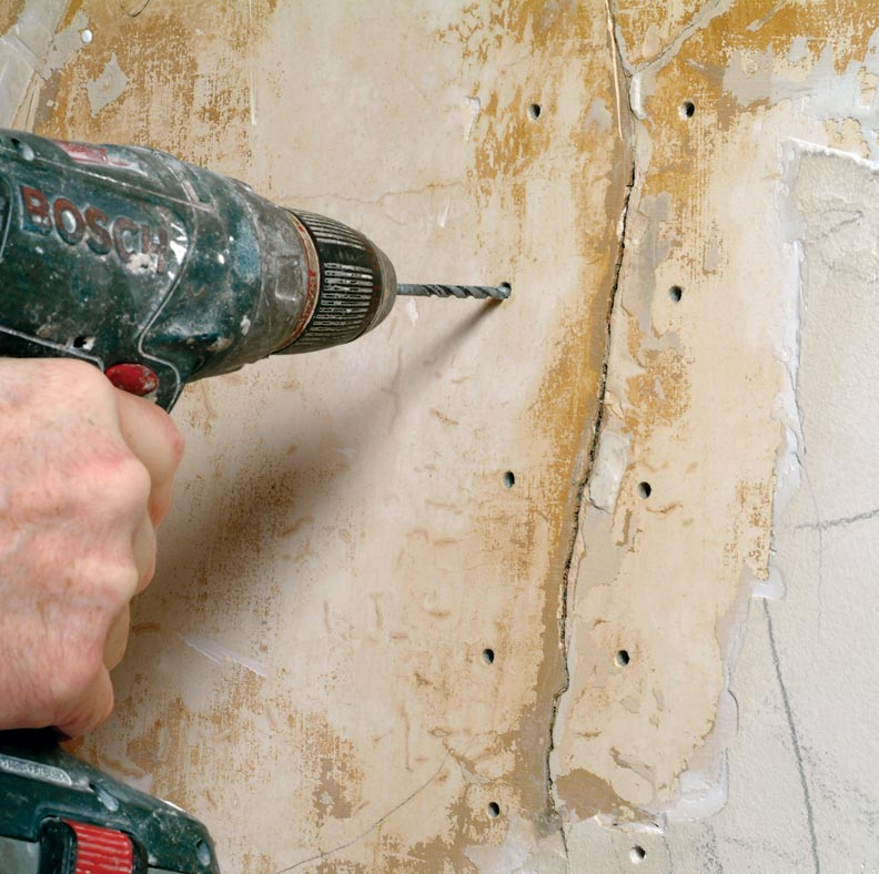 Drilling holes on either side of the plaster crack