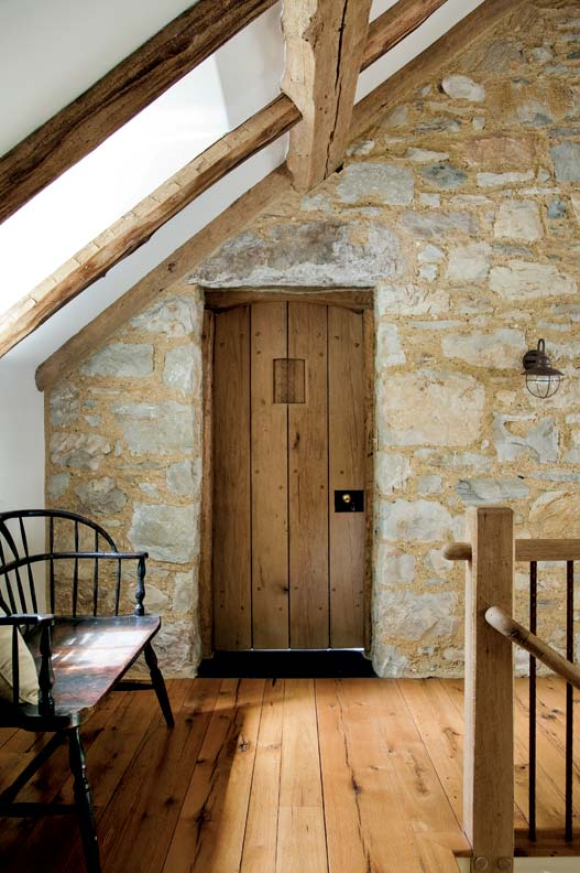 Authentic interiors include exposed stone walls in the second-floor hall.