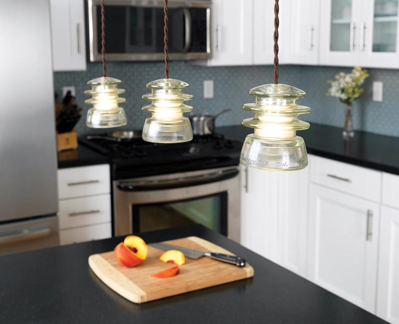 A trio of repurposed insulator pendants from Conant Metal & Light illuminates a counter.