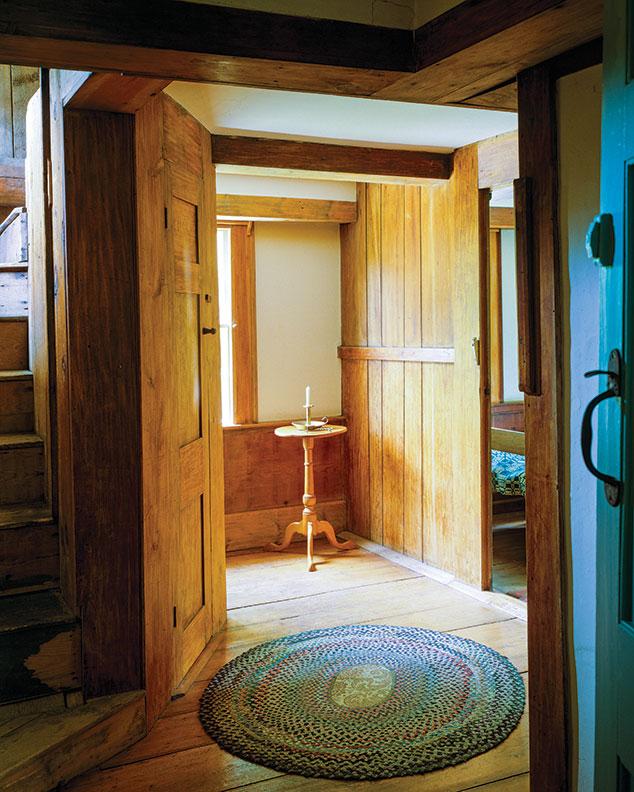 Plain pine board walls and wainscot furnish the upstairs hall.