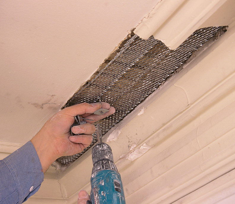 Expanded metal mesh is the modern lath common since the 1920s and widely used for large repairs. Here, a piece is cut to the patch shape and screwed right over the old wood lath to improve anchoring for the plaster scratch coat.