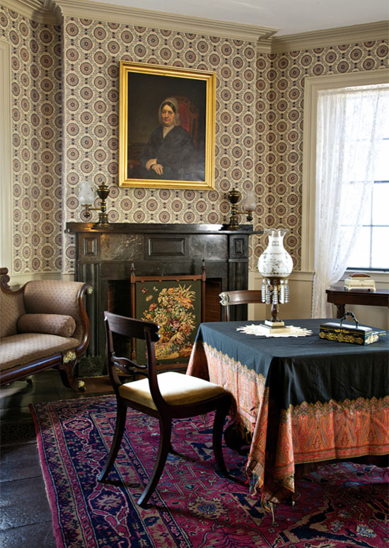 In the family parlor, Empire and Victorian furnishings coexist with the Federal-era wallpaper, reproduced by Adelphi from a Plymouth-area document in the archive of Historic New England.The portrait is of Eunice Denny Burr Hedge.