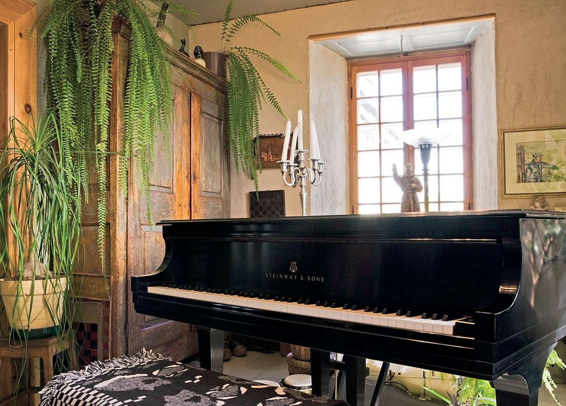 This side of the big living room is furnished as a music room, with frilly green plants around the Steinway grand piano.