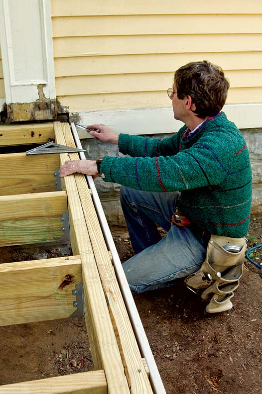 One of Ted's tricks for making porches that last is ensuring that parts have good ventilation; here, he accomplishes this by installing vertical shims between the exterior joist and the finish apron (the shims are visible in the gap between these two elements).