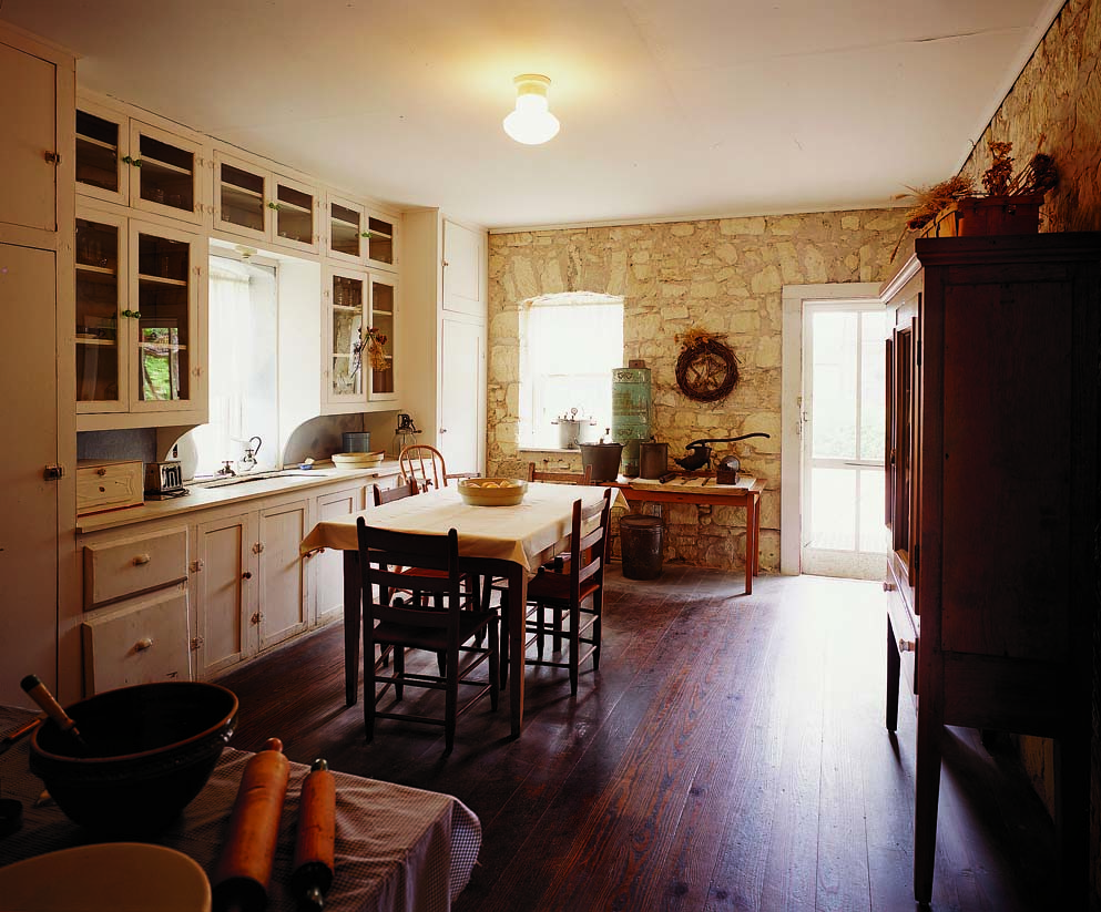 The kitchen in the Fassel-Roeder House in Fredericksburg, Texas, dates to 1858 and is unusual for its built-in wall of cabinets interspersed with worktables and a freestanding storage cupboard, the bare bones essentials of the time.