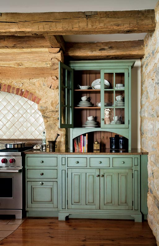 Rough-hewn beams and muted, colonial-inspired green create a classic kitchen feel in this Pennsylvania farmhouse.
