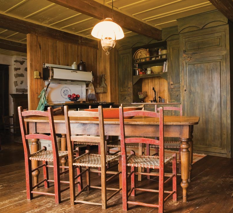 The kitchen disappears into the rustic interior. Cabinets that incorporate a sink were inspired by an antique buffet. The pine table and chairs are antique. A Heartland reproduction range fits the mood.