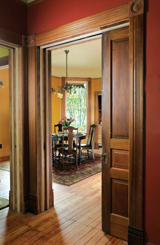 Millwork framing the 8'-tall pocket door (left) leading to the dining room is new, custom-cut to match surviving samples, but blends seamlessly with the antique door.