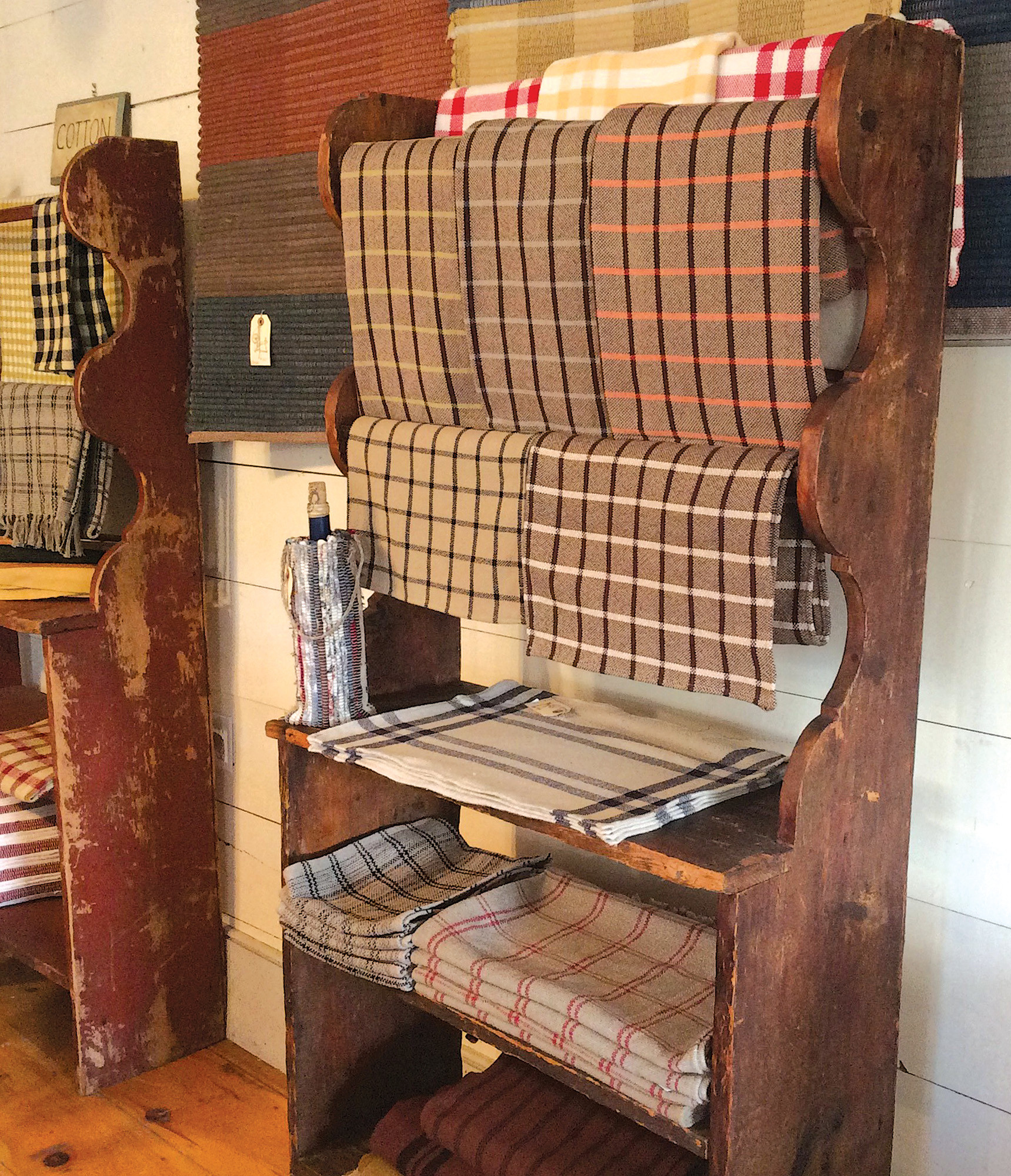 Ready-made textiles on a rack include tablecloths and runners.