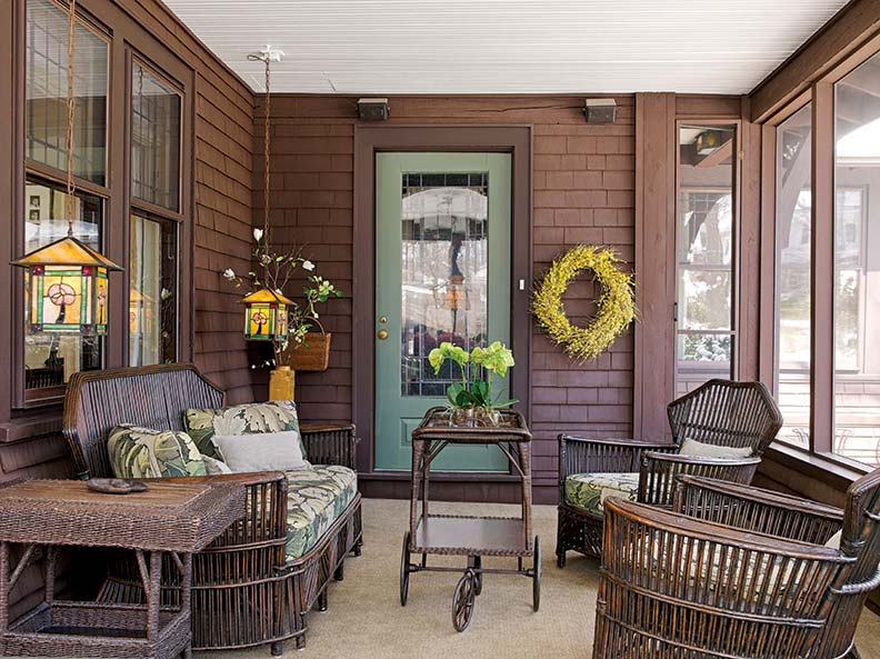 Rattan furniture and art glass lamps furnish the sun porch.