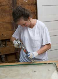 Pam carefully removes glazing compound (which had been painted green along with the window frame) from the sash.