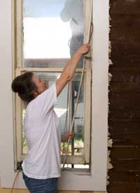 Pam begins the window restoration by removing nails and screws and carefully prying off trim and stops.