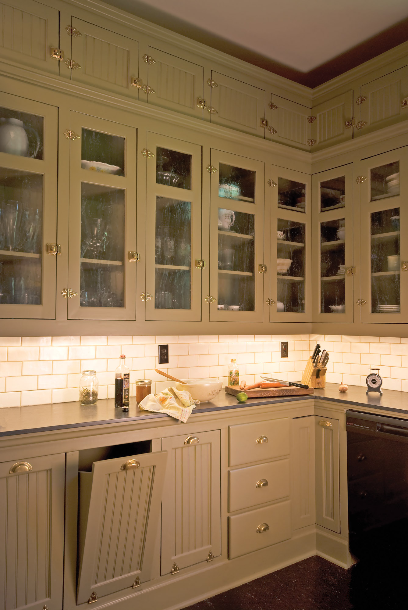 Reproduction is the way to go when outfitting an entire room, like this Arts & Crafts-era kitchen that needed a suite of latches, knobs, and bin pulls.