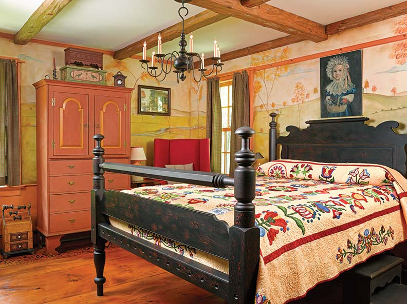 The black-painted mushroom bed was made by Bryce Ritter; it's dressed with a Pennsylvania quilt sewn by Tami Jones. Atop the tall chest sits an exact replica of a 1765 Berks County marriage box with bird decoration and a 1600s Connecticut carved miniature chest; both pieces are by Adam Mathews. Paul Rulli reproduced the watch hutch from an 1800s original.