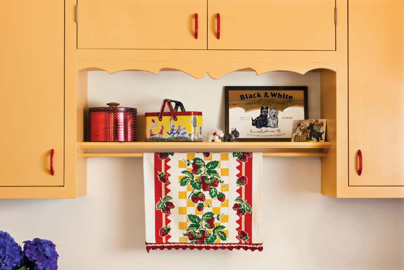 SOme favorite things from the owner's childhood sit on the display shelf under a cabinet trimmed in a scallop detail borrowed from the cabinets bought on Craigslist.