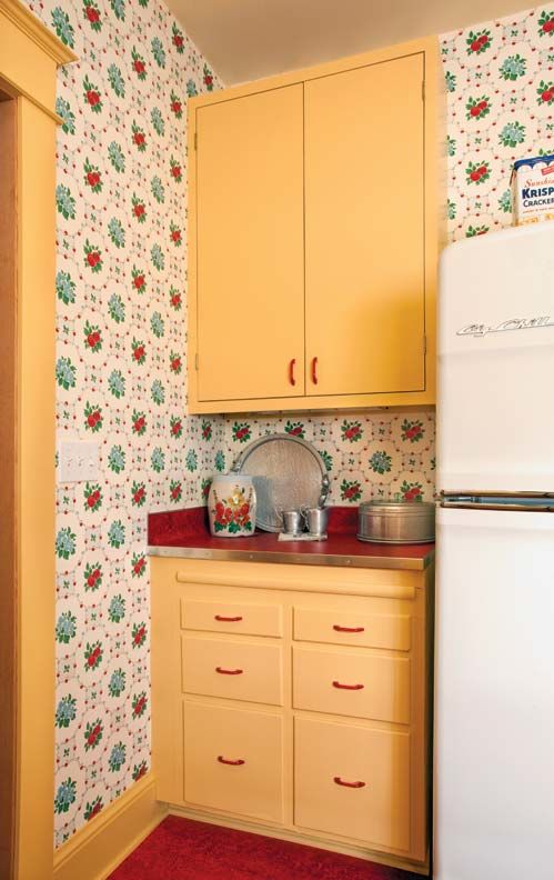 Colors of the era are echoed throughout the kitchen. Note, too, that the woodwork is painted the same color as cabinets. The sweet reproduction wallpaper clinches the look.
