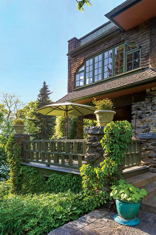 The alternating spindles on the deck railing resonate with the lines of casement windows on a circa 1910 stone and stucco house.