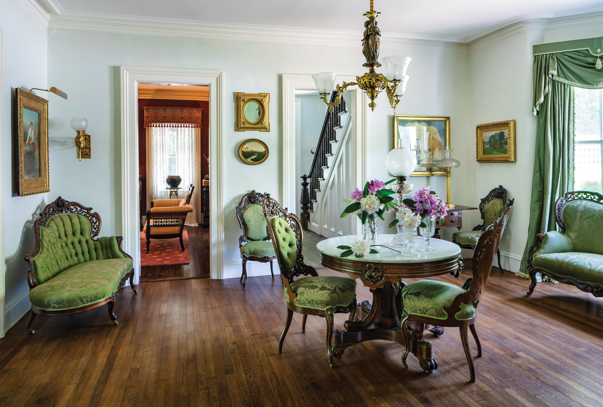 "The room has a delicately carved Meeks rosewood parlor set as well as a substantial center table the owner dubbed ""the Queen Mum."""