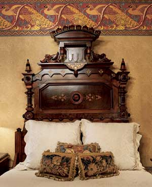 Floral tapestry pillows with deep ball fringe are the perfect counterpoint for a late-19th-century Renaissance Revival bed.