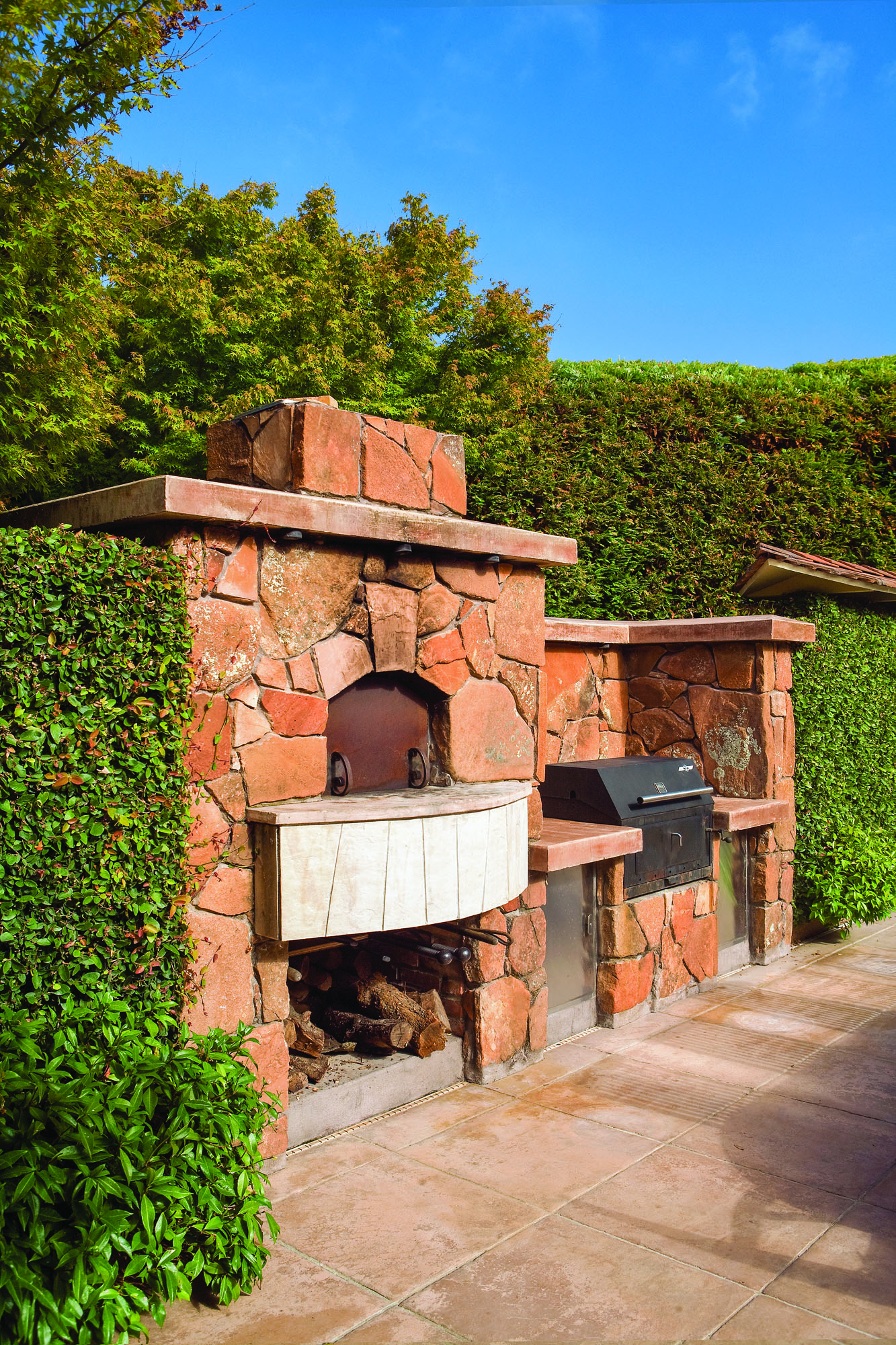 A pizza oven and grill sit side by side in this stone structure.