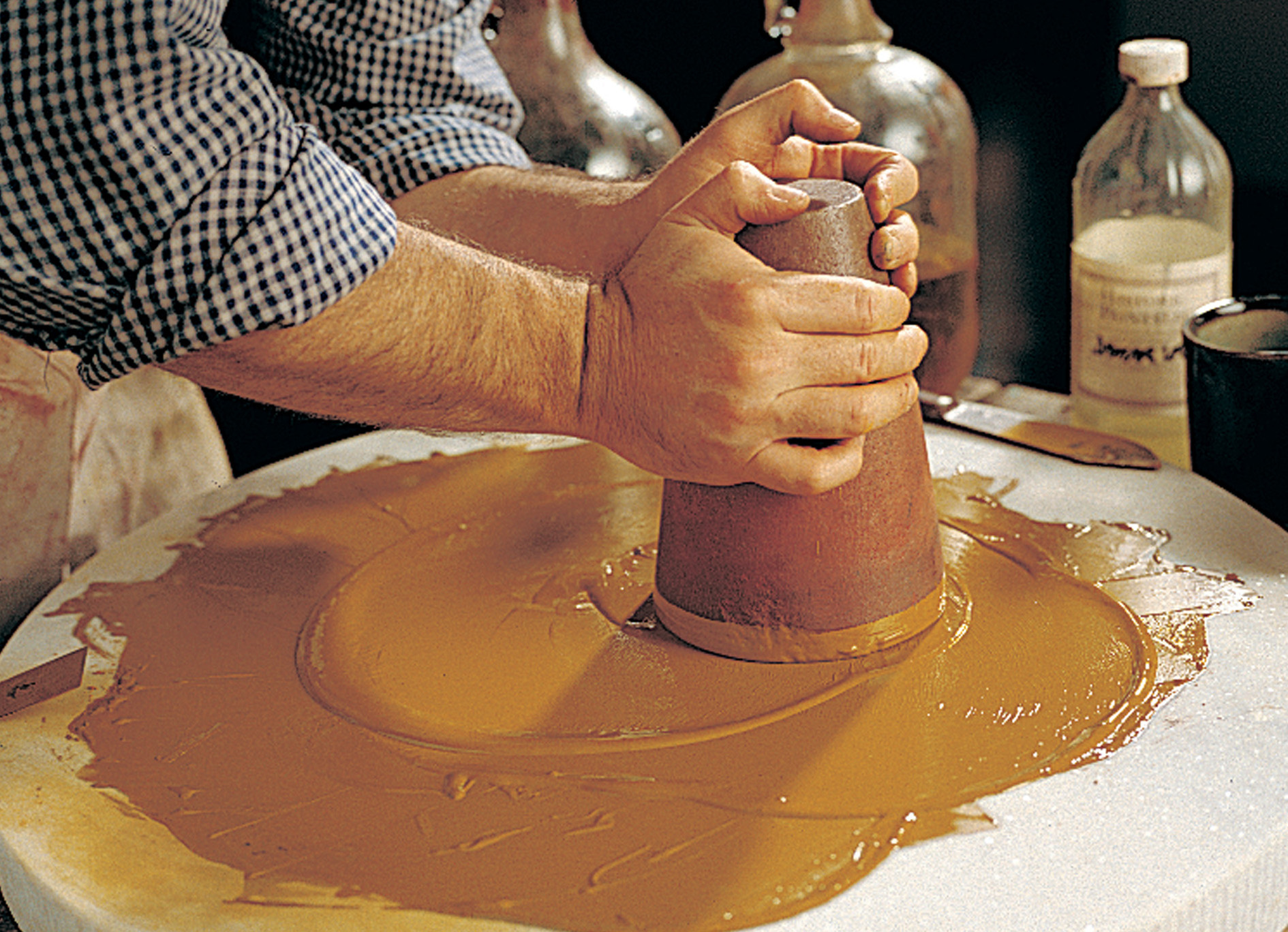 Before pre-mixed, store-bought paints were common, colors were mixed by hand. Here a muller is used to grind dry pigments into the binder (e.g., oil, casein).