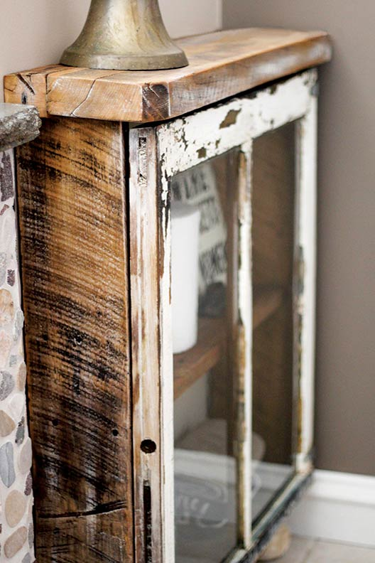 Bliss used reclaimed barnwood for her cabinet frame to match the patina of the antique window.