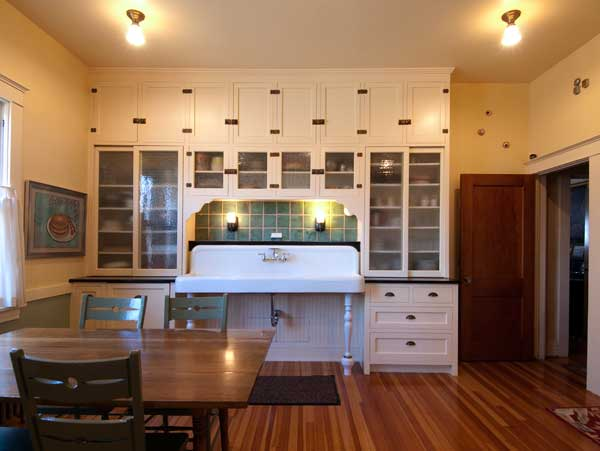 Salvaged and restored, the wall of cabinets and 6' sink are the centerpiece of the room. The owners prefer a versatile farm table rather than an island.