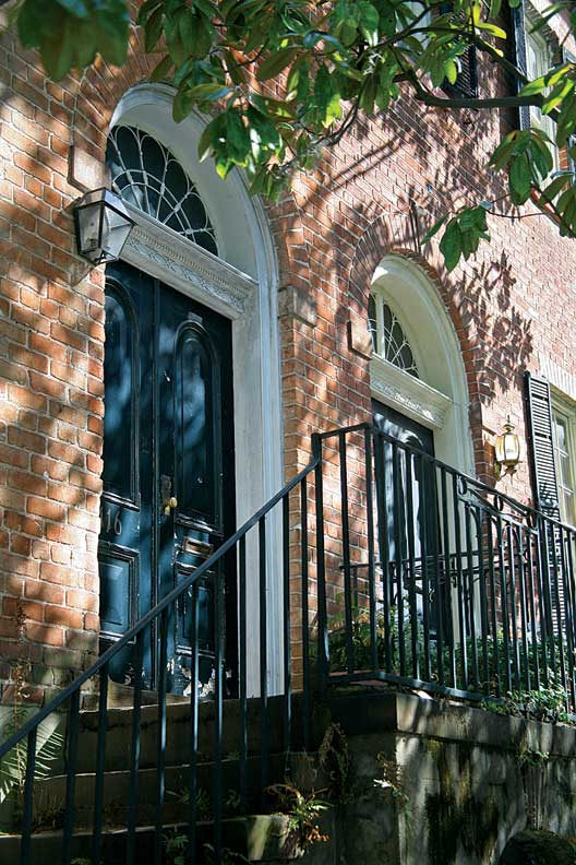 Arched, leaded fanlights distinguish this pair of brick Federal houses, while the doors have later Victorian arched panels.
