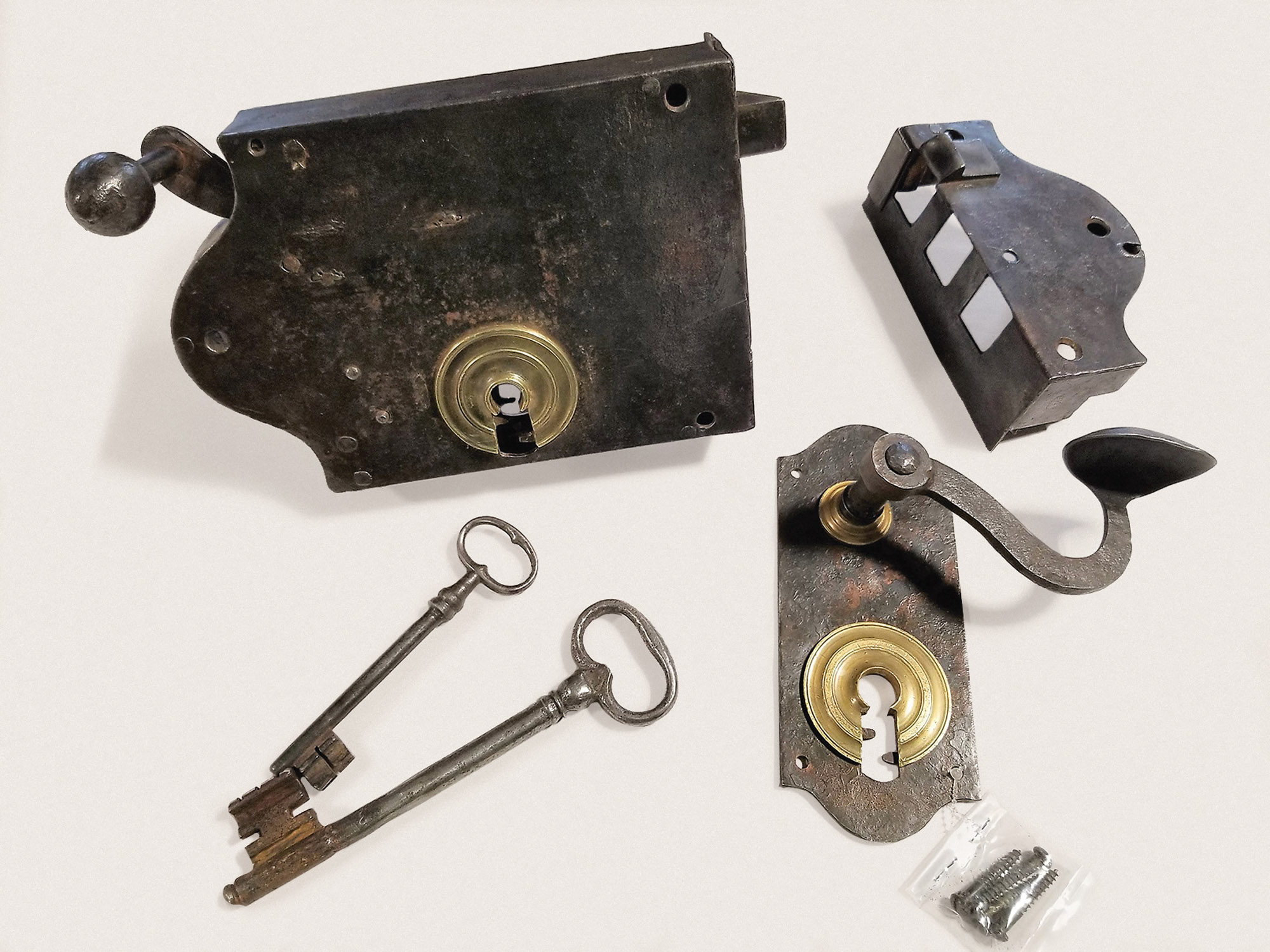 A homeowner who had part of a functioning, 17th-century iron-and-brass lock brought it to the team at Heritage Metalworks, who custom-forged a new trim plate and added brass details to match the original lock. Now the lock has a mating latch on the other side of the door.