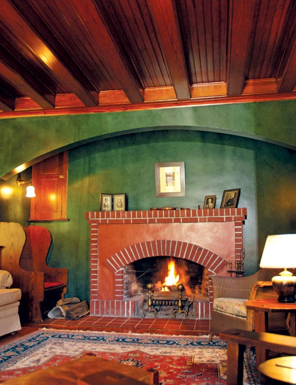 The inglenook includes Colonial Revival details: a fireplace crane, original brass andirons, and a parson's cabinet above the settle.