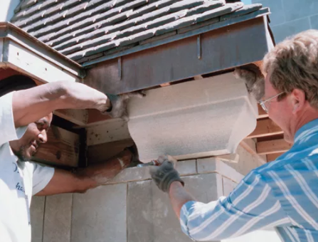 Robert Moses and Rick Tulles fit a cornice block on site and anchor it in place; a stonemason will tuck-point it with mortar.