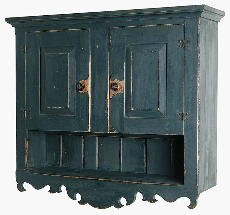Scroll-bottom, distressed-finish wall cupboard by Martin's Chair reproduces a Pennsylvania German antique.