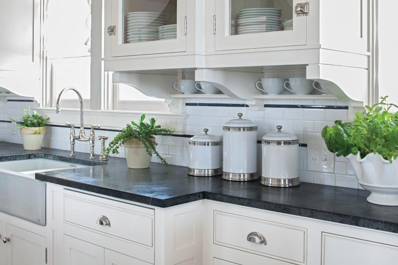 The countertops are made of soapstone, and the backsplash is white tile.