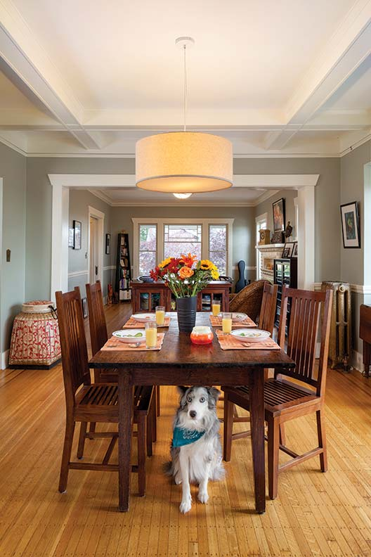 Bells, one of the family's Australian Shepherds, has a favorite spot under the dining-room table—which is made from an Indonesian door. The dining room and living room flow together.