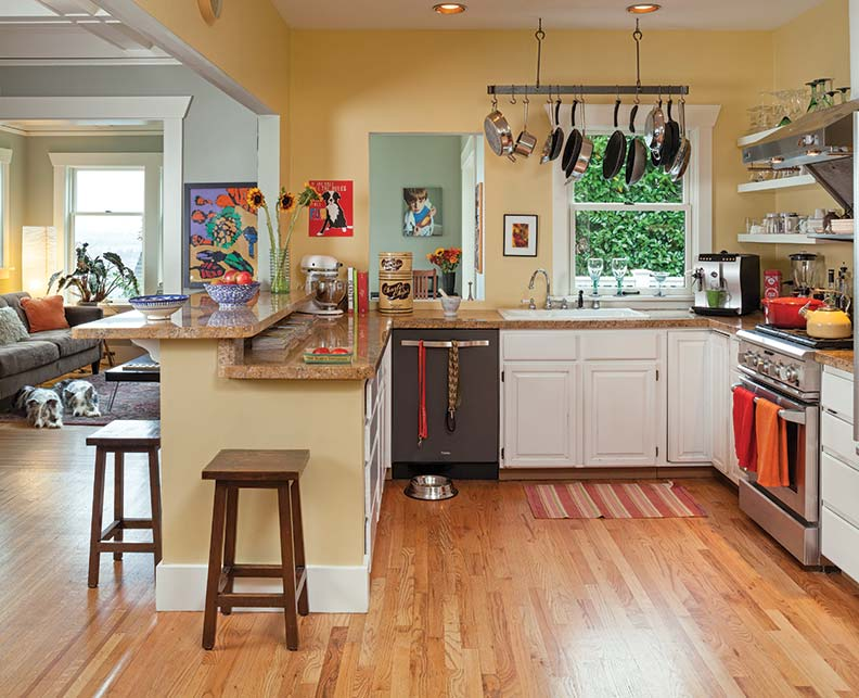 Open shelving in the kitchen helps keep the space light and airy; the family room is seen beyond.