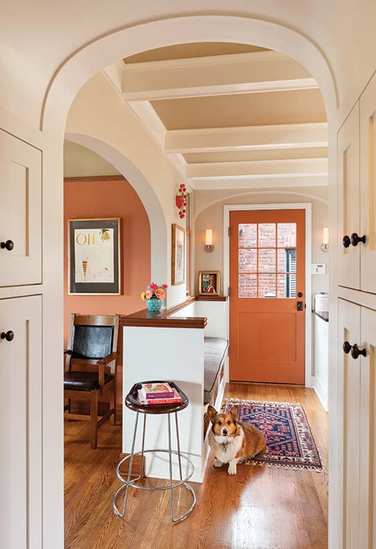 A pantry with an arched ceiling separates the new kitchen from the main hall with its built-in bench, where Yoda, a Pembroke Welsh Corgi, waits for dinner.