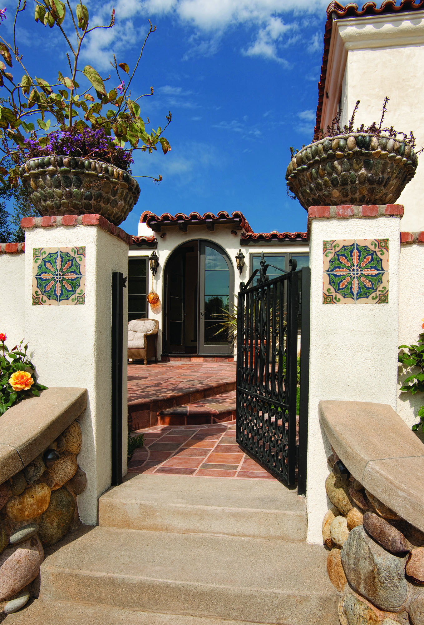 "Back and front iron gates, probably dating to the 1920s, came from a local antiques store. The tile inserts decorating the piers are original Tropico tiles collected by the homeowner, as ""unset"" units purchased in a box of two dozen."