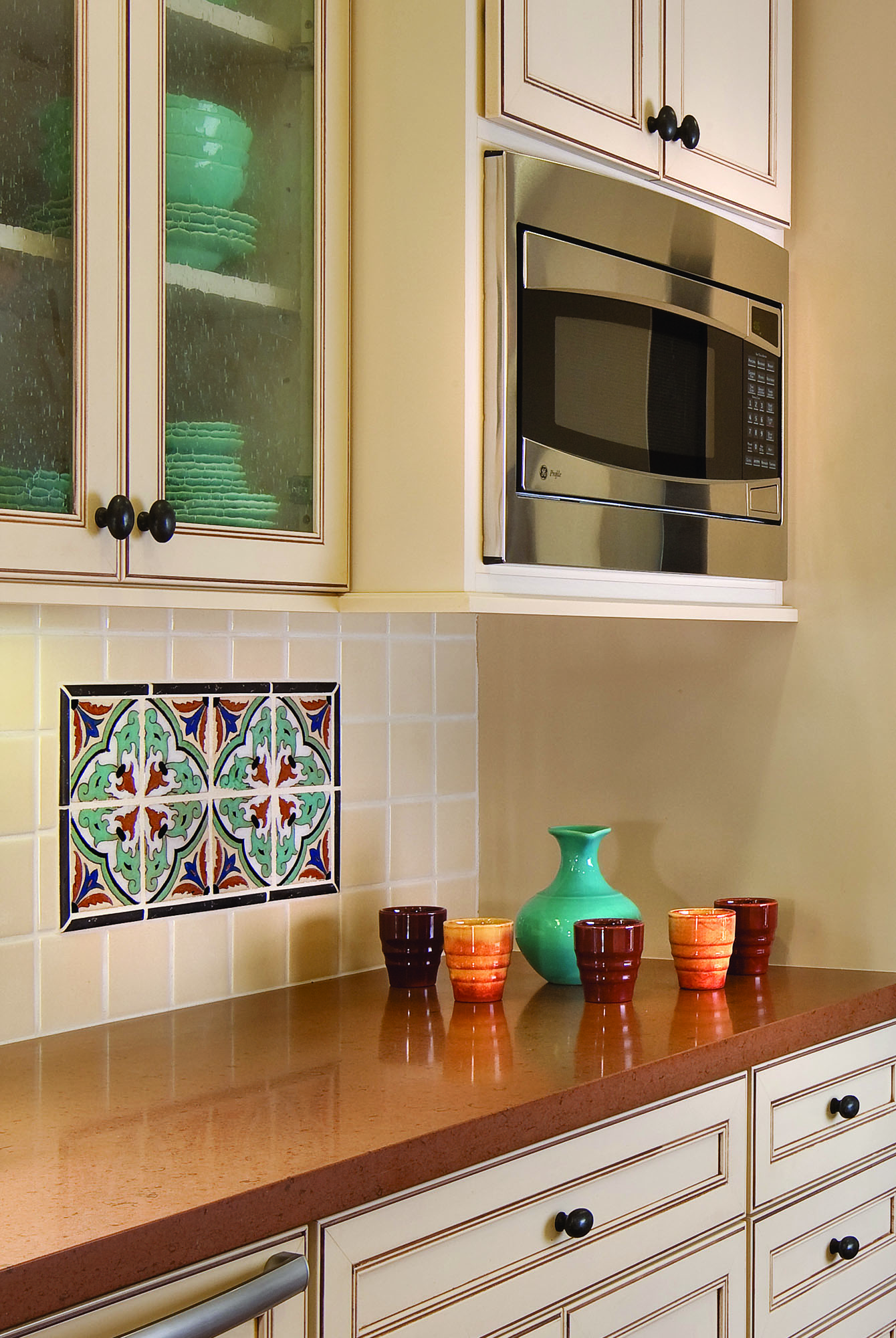 In the kitchen, antique tiles set into a generic field are Tropico (1920–23) tiles found by the homeowner.
