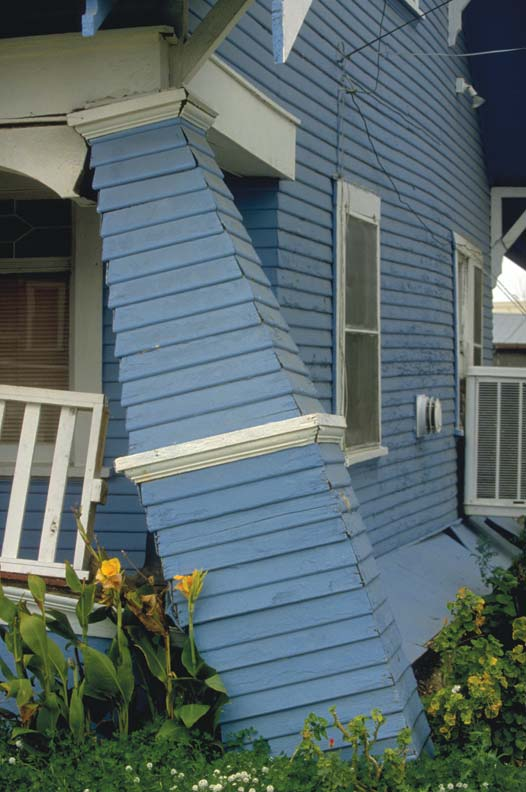 Because wood-frame houses are basically boxes, the power of earthquake forces works to collapse the structure by racking walls, separating joints, and upending vertical supports such as porch columns.